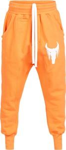 Pomarańczowe spodnie Robert Kupisz w sportowym stylu