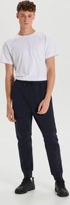 Granatowe spodnie sportowe Cropp z nadrukiem