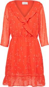 Pomarańczowa sukienka minimum na sylwestra z długim rękawem w kwiaty